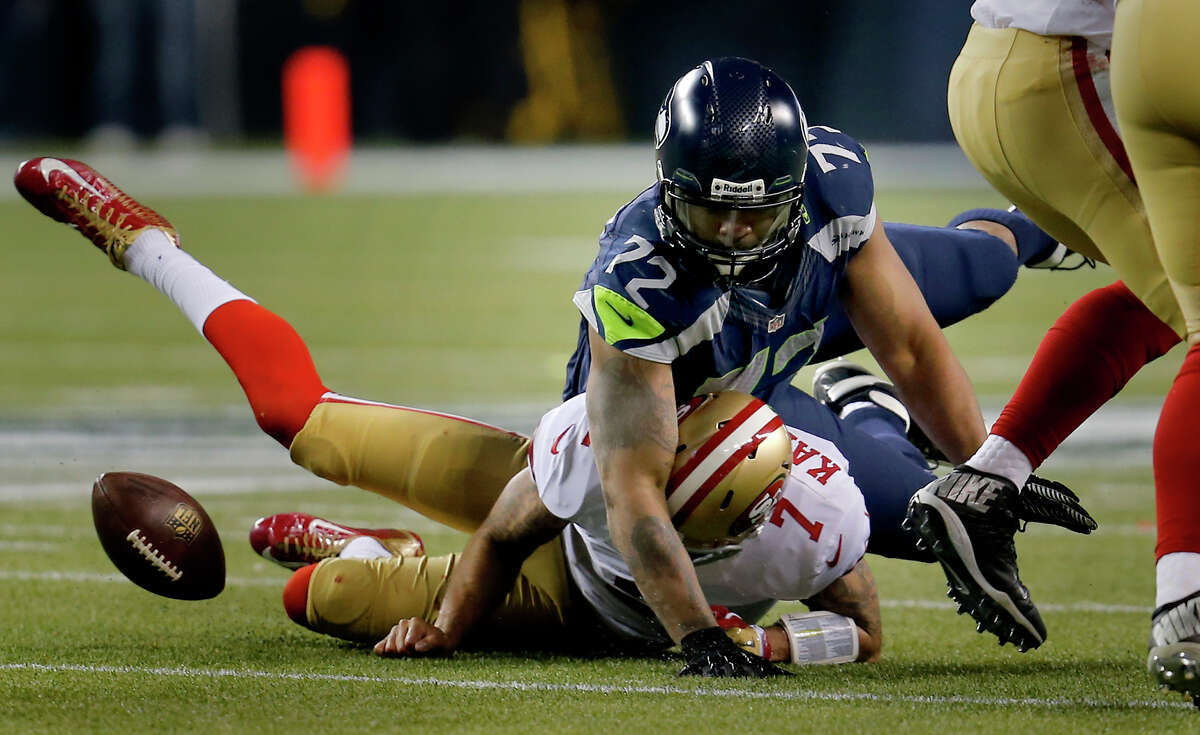 Colin Kaepernick (7) was tackled and fumbled the ball by Seattle's Michael Bennett (72) but the 49ers retained possession in the second half Sunday January 19, 2014. The Seattle Seahawks defeated the San Francisco 49ers 23-17 to win the NFC championship and a trip to the Super Bowl at CenturyLink Field in Seattle, Washington.