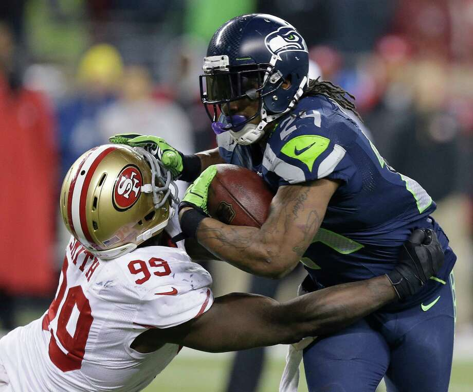 Seattle Seahawks' Marshawn Lynch tries to run past San Francisco 49ers' Aldon Smith during the second half of the NFL football NFC Championship game Sunday, Jan. 19, 2014, in Seattle. (AP Photo/Elaine Thompson)  ORG XMIT: NFC209 Photo: Elaine Thompson / AP