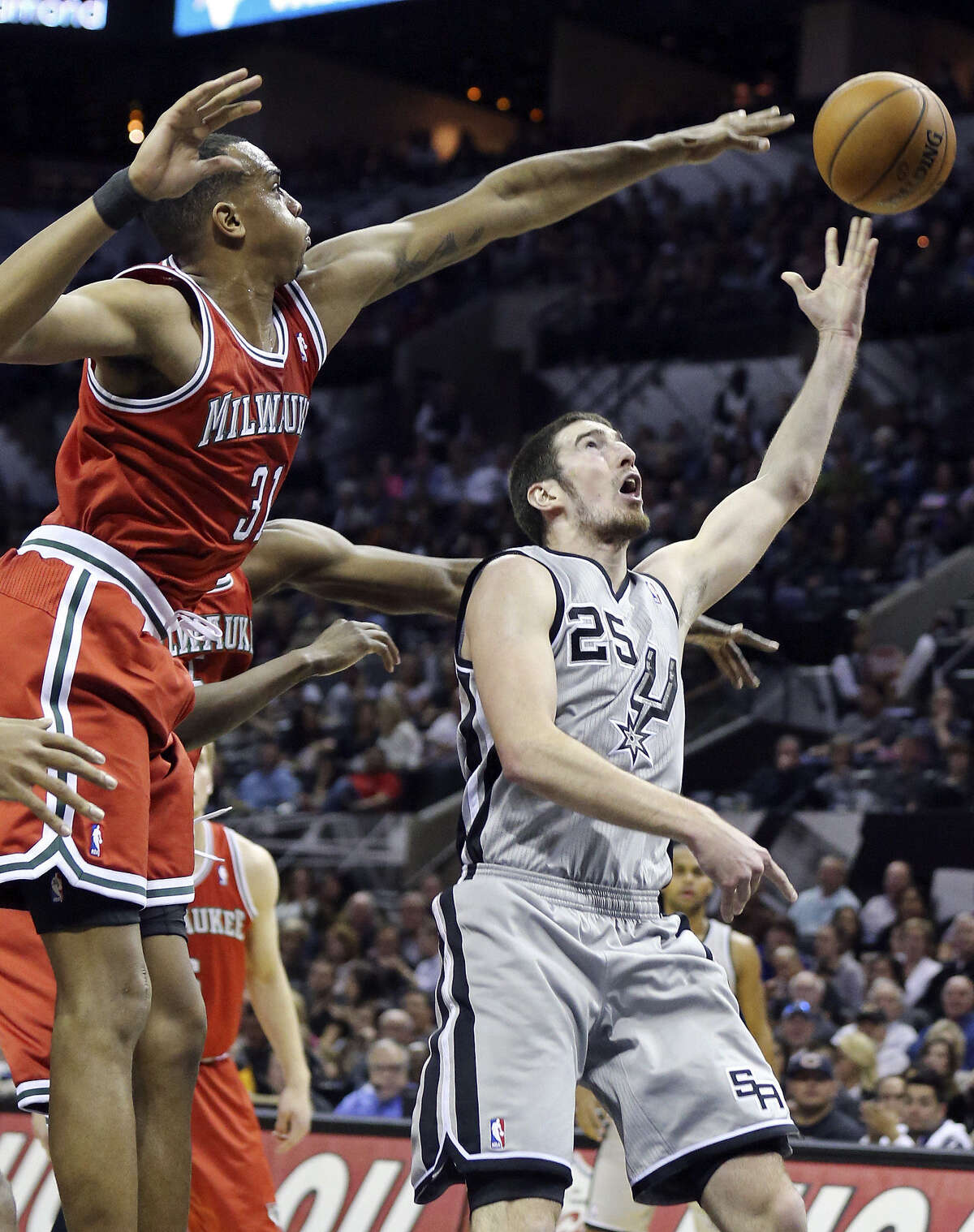 The Spurs' Nando De Colo, getting off a shot in the lane around Milwaukee's John Henson during the second half, got some rare extended playing time Sunday and finished with 13 points.