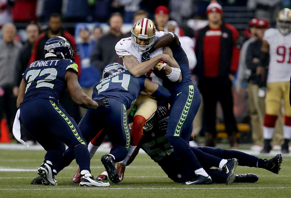 Colin Kaepernick (7) was tackled by a group of Seahawks in the first half Sunday January 19, 2014. The Seattle Seahawks defeated the San Francisco 49ers 23-17 to win the NFC championship and a trip to the Super Bowl at CenturyLink Field in Seattle, Washington.