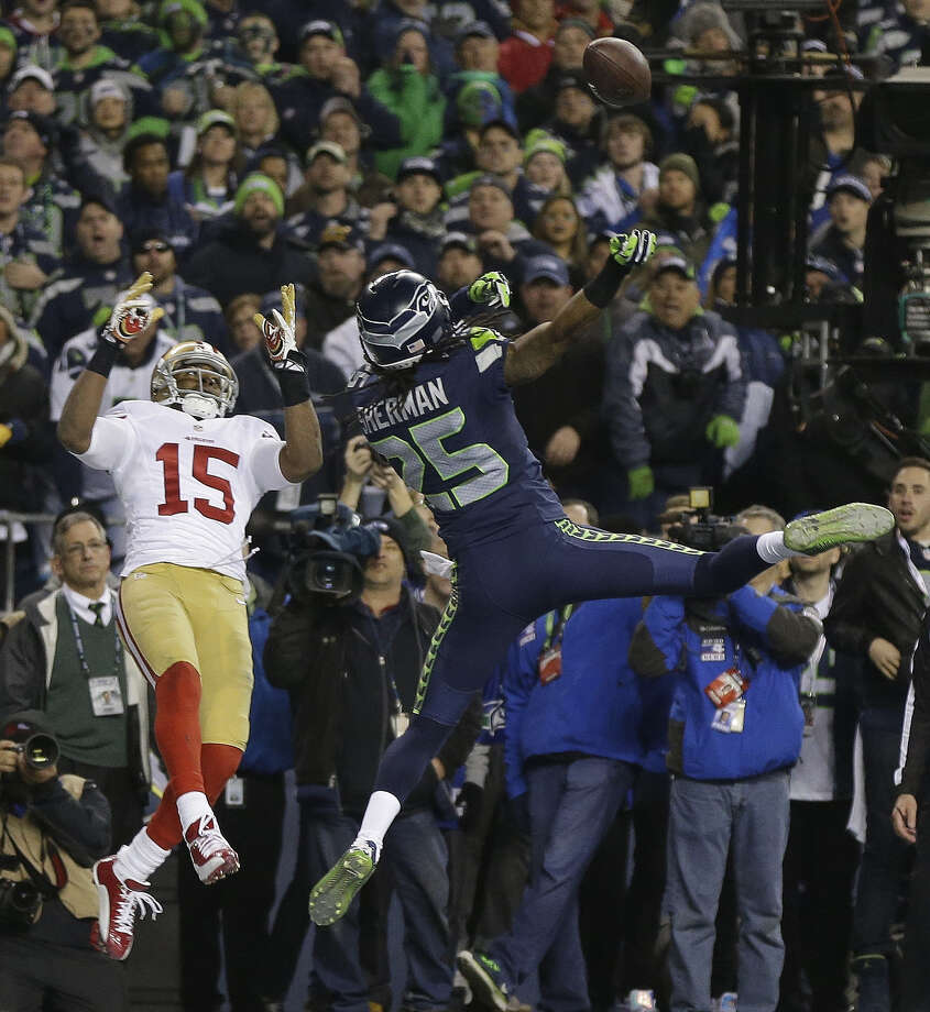 Cornerback Richard Sherman (right), who played for San Francisco coach Jim Harbaugh at Stanford, breaks up a pass intended for the 49ers' Michael Crabtree in the final seconds to preserve the NFC title for the Seahawks. Photo: Marcio Jose Sanchez / Associated Press / AP