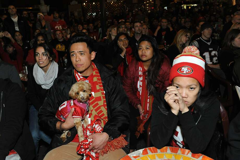 Daryl Tenazas (left) and Alyssa Aguirre (right) react at SoMa StrEat Food Park after the San Francisco 49ers lose to the Seattle Seahawks on January 19, 2014. Photo: Susana Bates, Special To The Chronicle
