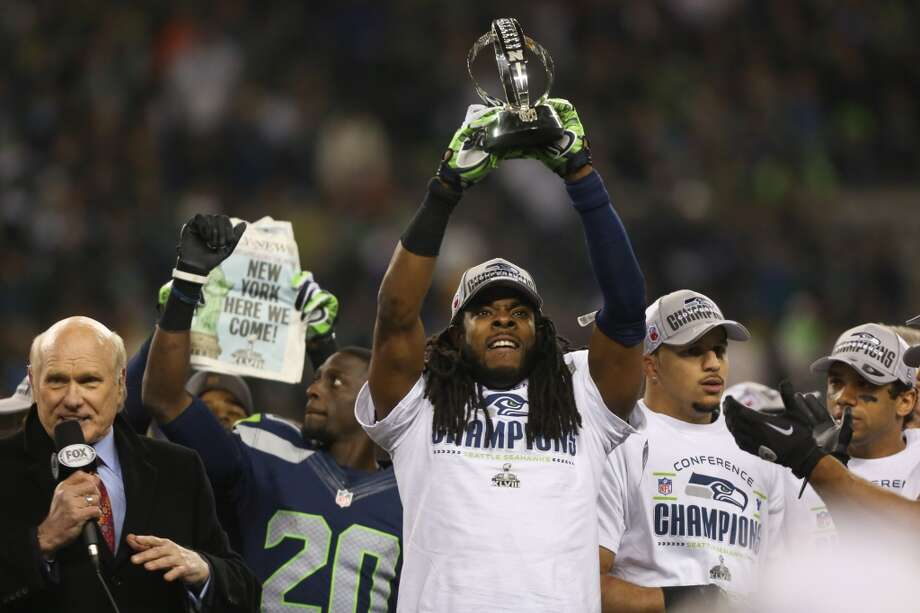 Seattle Seahawks player Richard Sherman hoists the NFC Championship trophy after the Seahawks defeated the San Francisco 49ers at CenturyLink Field on Sunday, January 19, 2014. (Joshua Trujillo, seattlepi.com) Photo: SEATTLEPI.COM