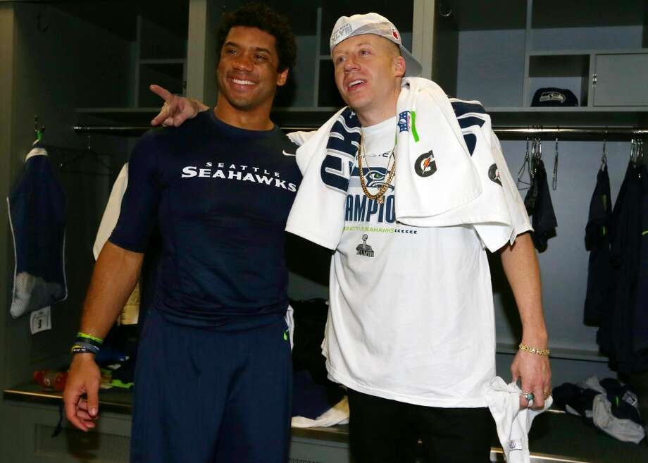 SEATTLE, WA - JANUARY 19:  Quarterback Russell Wilson #3 and rapper Macklemore celebrate in the locker room after the Seahawks 23-17 victory against the San Francisco 49ers during the 2014 NFC Championship at CenturyLink Field on January 19, 2014 in Seattle, Washington.  (Photo by Ronald Martinez/Getty Images) Photo: Getty Images