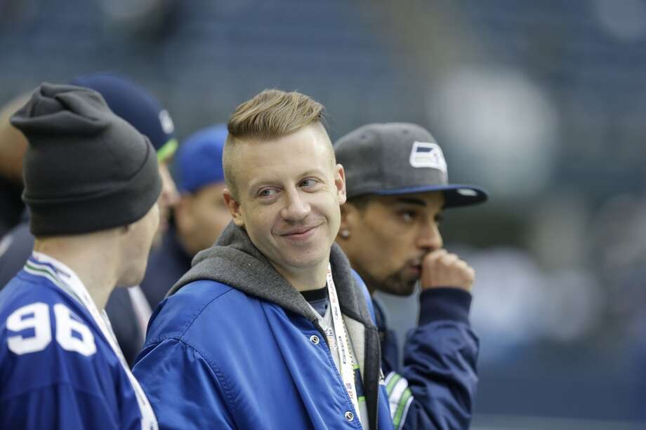 Rapper Macklemore speaks to fans before the NFL football NFC Championship game between the Seattle Seahawks and the San Francisco 49ers Sunday, Jan. 19, 2014, in Seattle. (AP Photo/Elaine Thompson) Photo: AP