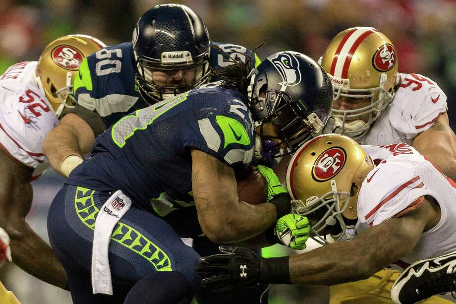 Seahawks running back Marshawn Lynch, center, is battered by 49ers defense during the first half of the NFC Championship game Sunday, Jan. 19, 2014, at CenturyLink Field in Seattle. Photo: JORDAN STEAD, SEATTLEPI.COM / SEATTLEPI.COM