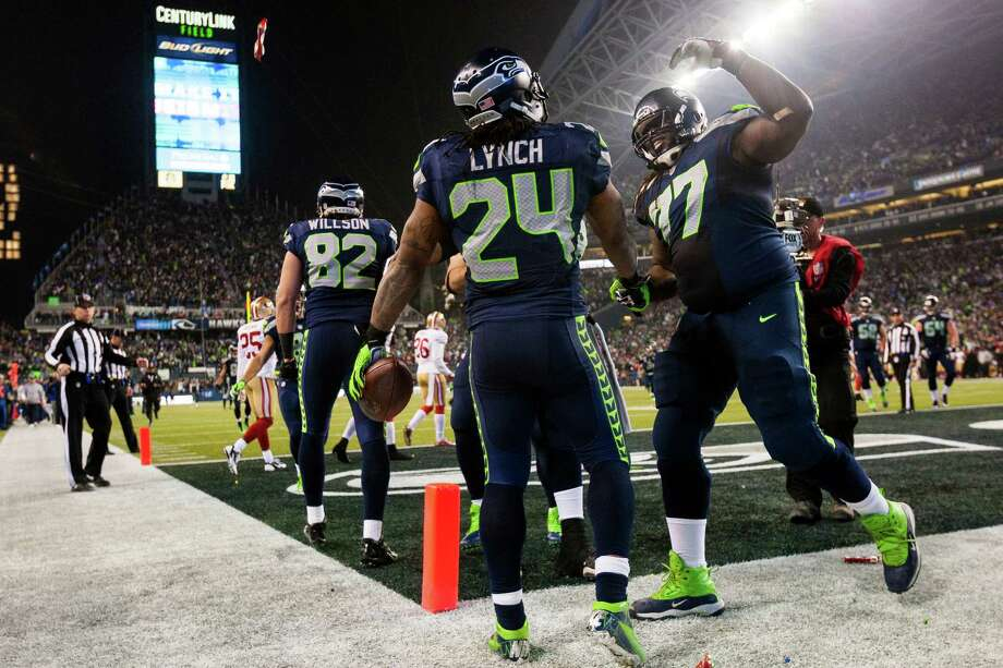 Seahawks running back Marshawn Lynch, center, is congratulated by teammates after rolling past 49ers defense to score a touchdown during the first half of the NFC Championship game Sunday, Jan. 19, 2014, at CenturyLink Field in Seattle. Photo: JORDAN STEAD, SEATTLEPI.COM / SEATTLEPI.COM