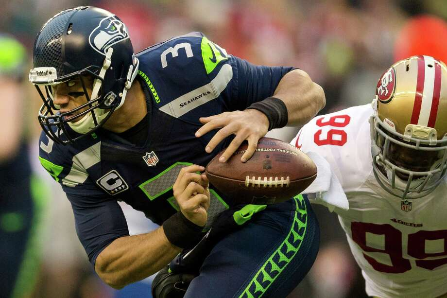 Seahawks quarterback Russell Wilson, left, fumbles the ball on the first play during the first half of the NFC Championship game against the San Francisco Chronicle Sunday, Jan. 19, 2014, at CenturyLink Field in Seattle. Photo: JORDAN STEAD, SEATTLEPI.COM / SEATTLEPI.COM
