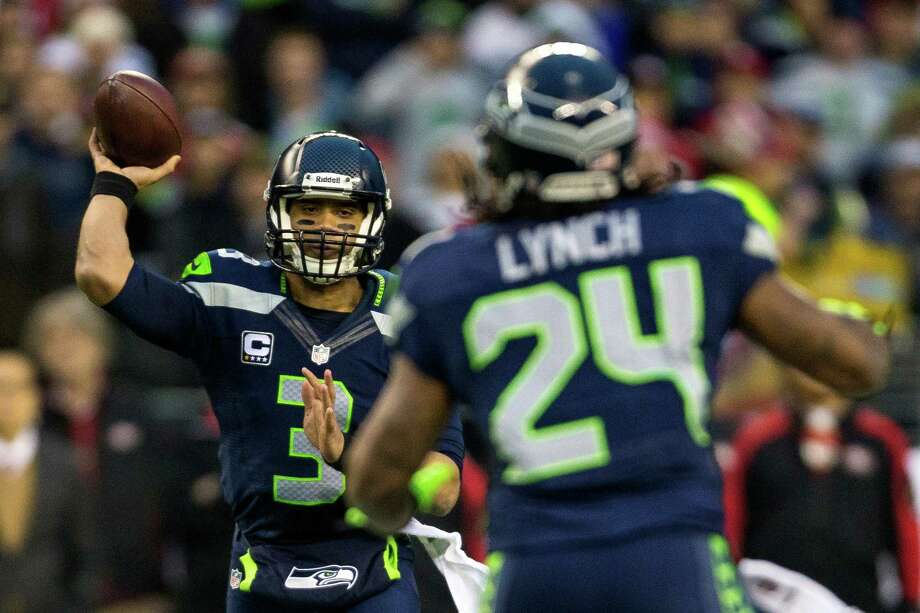 Quarterback Russell Wilson, left, passes to running back Marshawn Lynch, right, during the first half of the NFC Championship game Sunday, Jan. 19, 2014, at CenturyLink Field in Seattle. Photo: JORDAN STEAD, SEATTLEPI.COM / SEATTLEPI.COM