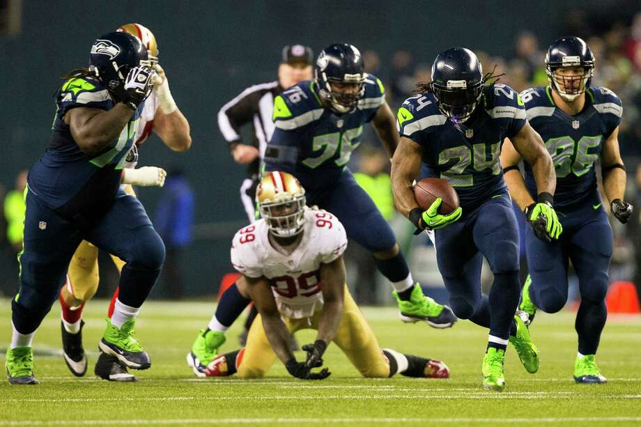 Seahawks running back Marshawn Lynch, right, pushes through 49ers defense during the first half of the NFC Championship game Sunday, Jan. 19, 2014, at CenturyLink Field in Seattle. Photo: JORDAN STEAD, SEATTLEPI.COM / SEATTLEPI.COM