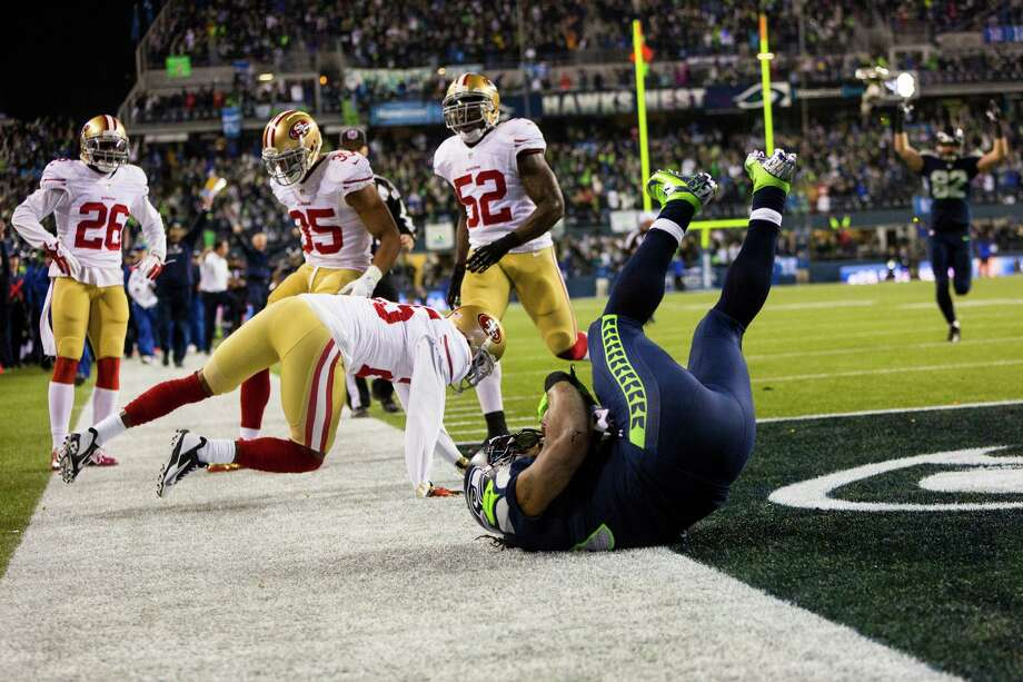 Seahawks running back Marshawn Lynch, center, rolls past 49ers defense to score a touchdown during the first half of the NFC Championship game Sunday, Jan. 19, 2014, at CenturyLink Field in Seattle. Photo: JORDAN STEAD, SEATTLEPI.COM / SEATTLEPI.COM