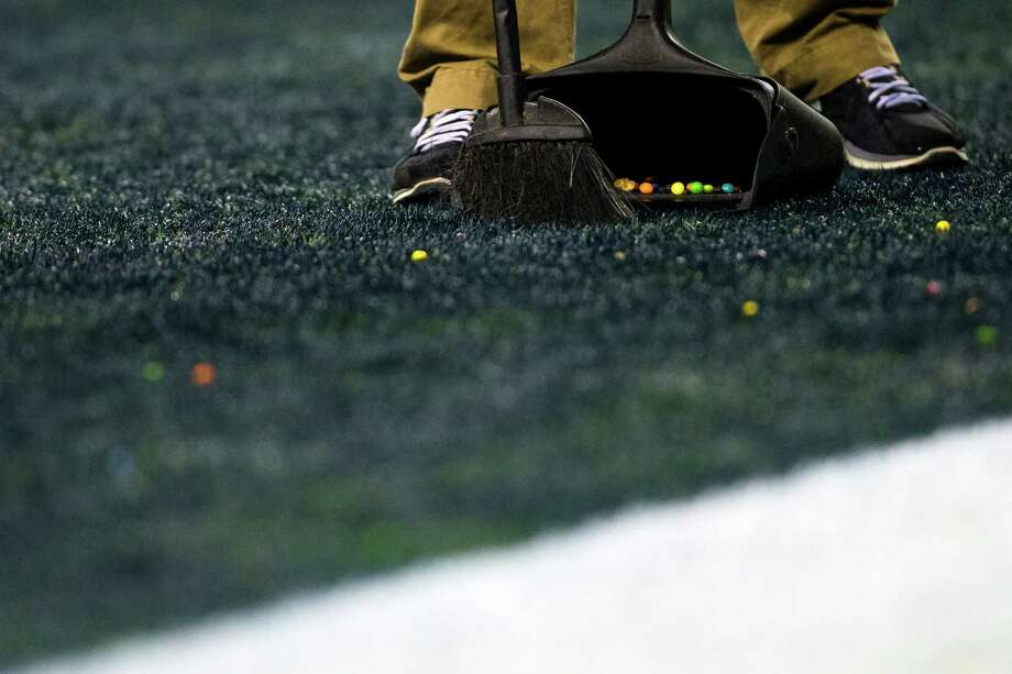 A field worker cleans up scattered Skittles following a Marshawn Lynch touchdown during the second half of the NFC Championship game Sunday, Jan. 19, 2014, at CenturyLink Field in Seattle. The Seahawks beat the 49ers 23-17 and will face off against the Denver Broncos in the Super Bowl on Feb. 2. Photo: JORDAN STEAD, SEATTLEPI.COM / SEATTLEPI.COM