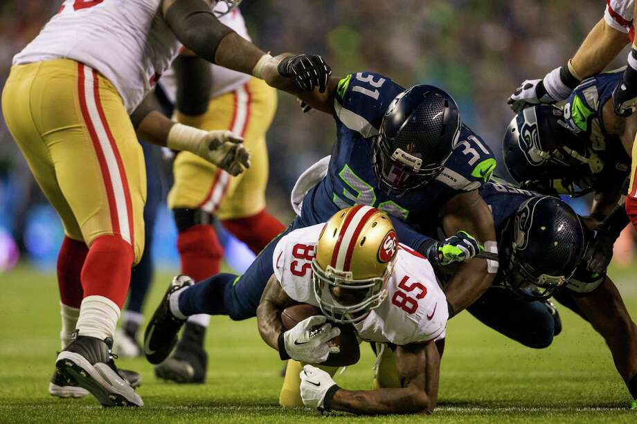 Seahawk Kam Chancellor, center top, throws a 49ers player to the ground just short of a touchdown during the second half of the NFC Championship game Sunday, Jan. 19, 2014, at CenturyLink Field in Seattle. The Seahawks beat the 49ers 23-17 and will face off against the Denver Broncos in the Super Bowl on Feb. 2. Photo: JORDAN STEAD, SEATTLEPI.COM / SEATTLEPI.COM