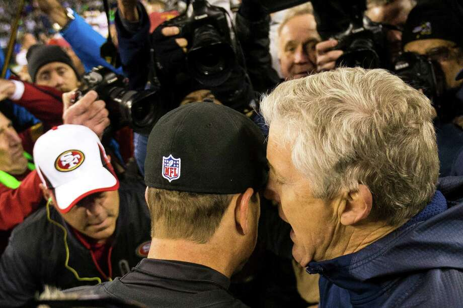 Seahawks head coach Pete Carroll, right, has an exchange with 49ers head coach Jim Harbaugh, center left, following a 23-17 win over the San Francisco 49ers at the NFC Championship game Sunday, Jan. 19, 2014, at CenturyLink Field in Seattle. The Seahawks will face off against the Denver Broncos in the Super Bowl on Feb. 2. Photo: JORDAN STEAD, SEATTLEPI.COM / SEATTLEPI.COM