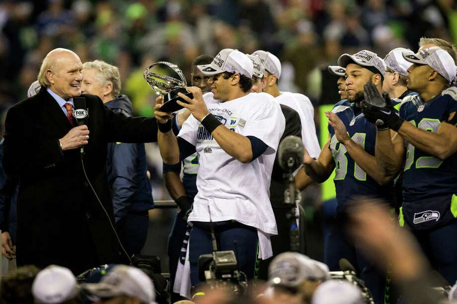 Seahawks quarterback Russell Wilson, center, hoists the NFC Championship trophy following a 23-17 win over the San Francisco 49ers Sunday, Jan. 19, 2014, at CenturyLink Field in Seattle. The Seahawks will face off against the Denver Broncos in the Super Bowl on Feb. 2. Photo: JORDAN STEAD, SEATTLEPI.COM / SEATTLEPI.COM