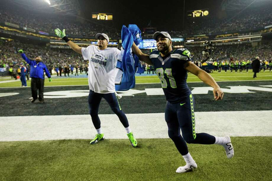 "Seahawk Golden Tate, right, runs around the field holding a ""12th Man"" flag following a 23-17 win over the San Francisco 49ers at the NFC Championship game Sunday, Jan. 19, 2014, at CenturyLink Field in Seattle. The Seahawks will face off against the Denver Broncos in the Super Bowl on Feb. 2. Photo: JORDAN STEAD, SEATTLEPI.COM / SEATTLEPI.COM"