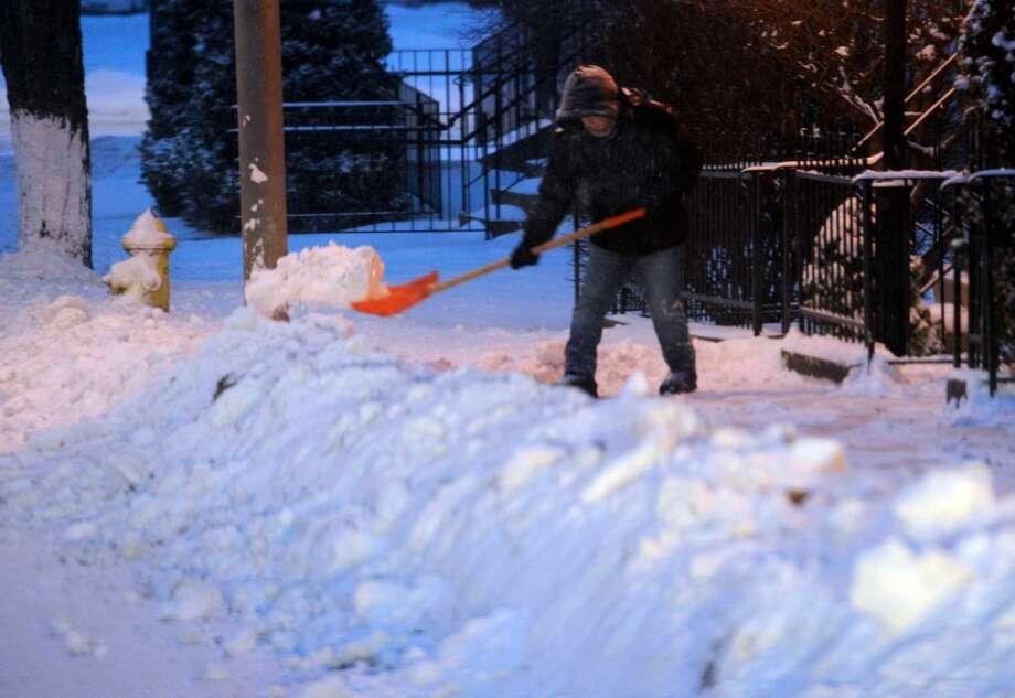 A worker shovels the snow from a sidewalk on Liberty Street in Danbury, Conn. Friday, Jan. 3, 2013. Photo: Carol Kaliff