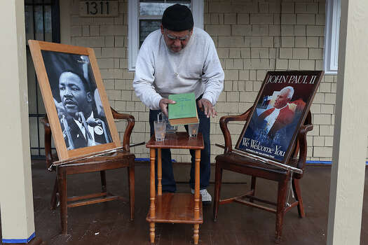 "At 1311 Martin Luther King Boulevard, George Bernal, 66, sets up a display at his mother's house, Monday, Jan. 20, 2014. The display features portraits of Martin Luther King, Jr. and Pope John Paul II, ""having a conversation with a glass of water,"" Bernal said. An expected crowd of over 100,000 people will participate in the march along the boulevard ending at Pitman-Sullivan Park. Photo: Jerry Lara, San Antonio Express-News / ©2013 San Antonio Express-News"
