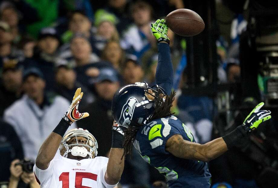 Seattle Seahawks cornerback Richard Sherman tips the ball away from San Francisco 49ers wide receiver Michael Crabtree and the ball is intercepted by Seattle Seahawks player Malcolm Smith during the NFC Championship game. Photo: AP