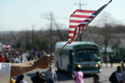 An American flag is waved as a 1950's vintage bus, representing what Rosa Parks and other civil rights pioneers did during the civil rights era, passes during the San Antonio Martin Luther King Jr. March on Monday, Jan. 20, 2014. Photo: Billy Calzada, San Antonio Express-News / San Antonio Express-News