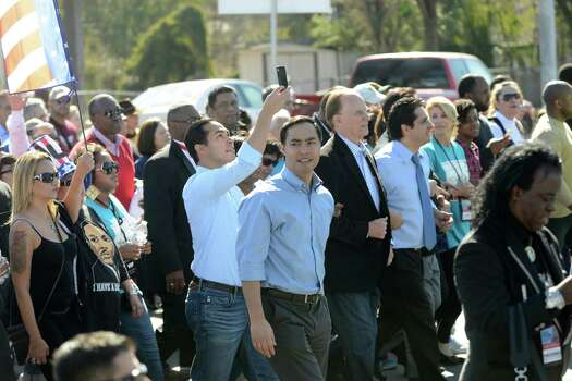 Rep. Joaquin Castro looks around as his brother, Mayor Julian Castro, snaps a picture during the San Antonio Martin Luther King Jr. March on Monday, Jan. 20, 2014. Photo: Billy Calzada, San Antonio Express-News / San Antonio Express-News
