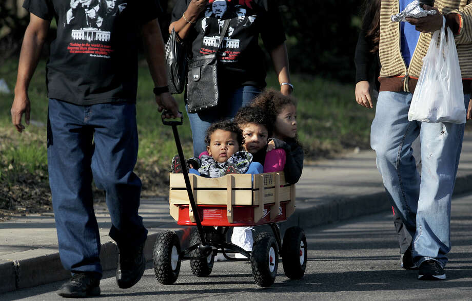 Beau Jenkins,1, (in wagon,front) Gregory Jenkins,4, and Nevaeh Jenkins,5, (rear of wagon) ride in a wagon during the Martin Luther King march Monday January 20, 2014. Photo: JOHN DAVENPORT, SAN ANTONIO EXPRESS-NEWS / ©San Antonio Express-News/Photo may be sold to the public