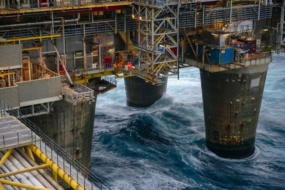 Workers move along an access way above the giant supporting legs of the Oseberg A offshore gas platform operated by Statoil ASA in the Oseberg North Sea oil field 140 kilometers  (87 miles) from Bergen, Norway, on Friday, Jan. 17, 2014. Photo: Kristian Helgesen, Bloomberg