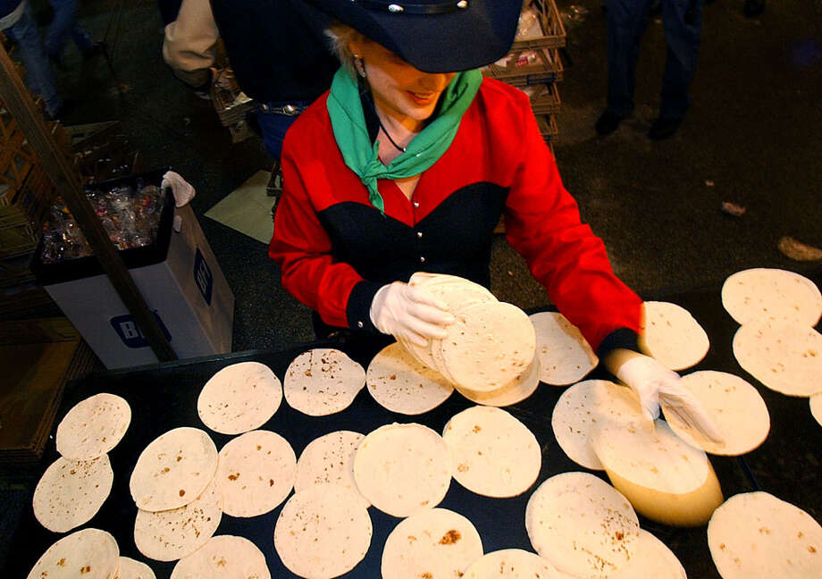 34,000 tortillasSusie Henckel spreads out a stack of tortillas like a blackjack dealer as she helps prepare breakfast tacos at the annual Cowboy Breakfast at Crossroads Mall on Jan. 30, 2004. Photo: KIN MAN HUI, San Antonio Express-News / SAN ANTONIO EXPRESS-NEWS