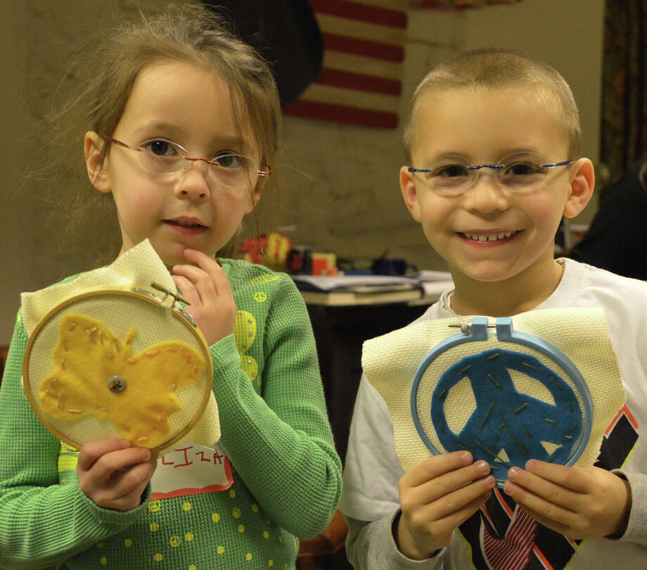 Eliza and Jonny Greenspan, both 5, of Westport, display peace-themed cross-stitch samples they created Monday during the Martin Luther King Day workshop at the Westport Historical Society. Photo: Jarret Liotta / Westport News contributed