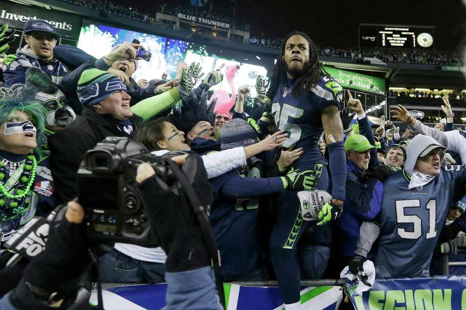 Seattle Seahawks' Richard Sherman celebrates with fans after after the NFL football NFC Championship game against the San Francisco 49ers Sunday, Jan. 19, 2014, in Seattle. The Seahawks won 23-17 to advance to Super Bowl XLVIII. Photo: Elaine Thompson, AP / AP2014