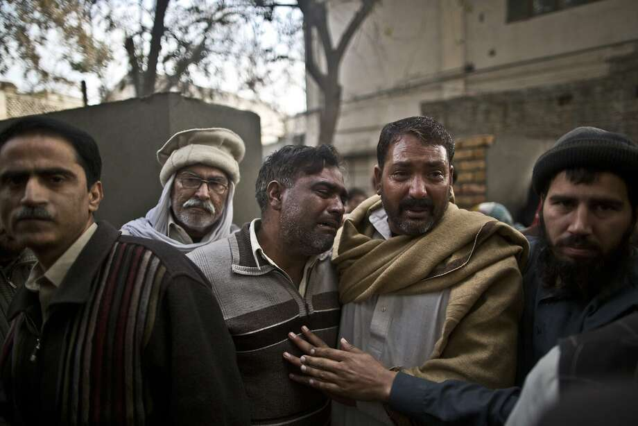 Two uncles (center) of Zoubair Latif, 17, comfort each other at a hospital in Rawalpindi as the Pakistani student's body is loaded into an ambulance to be taken away for burial after a suicide bombing Monday. Photo: Muhammed Muheisen, Associated Press