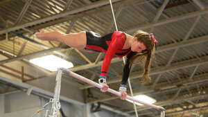 Warde's Tori Gallati competes on the uneven bars during the gymnastic meet against Ludlowe High School at Gymnastics & Cheer Academy in Fairfield on Monday, Jan. 20, 2014.