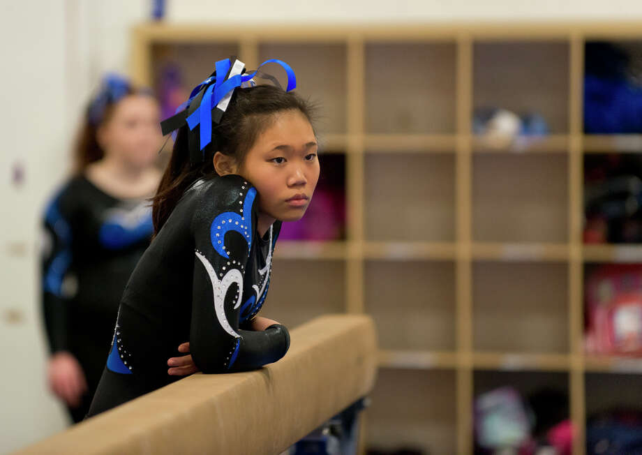 Ludlowe's Cate Seymour watches the floor competition during the gymnastic meet against Warde High School at Gymnastics & Cheer Academy in Fairfield on Monday, Jan. 20, 2014. Photo: Amy Mortensen / Connecticut Post Freelance