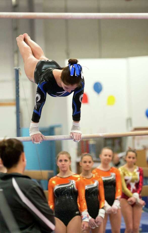 Ludlowe's Nicole Huntsman competes on the uneven bars as Shelton competitors look on during the gymnastic meet against Warde High School at Gymnastics & Cheer Academy in Fairfield on Monday, Jan. 20, 2014. Photo: Amy Mortensen / Connecticut Post Freelance
