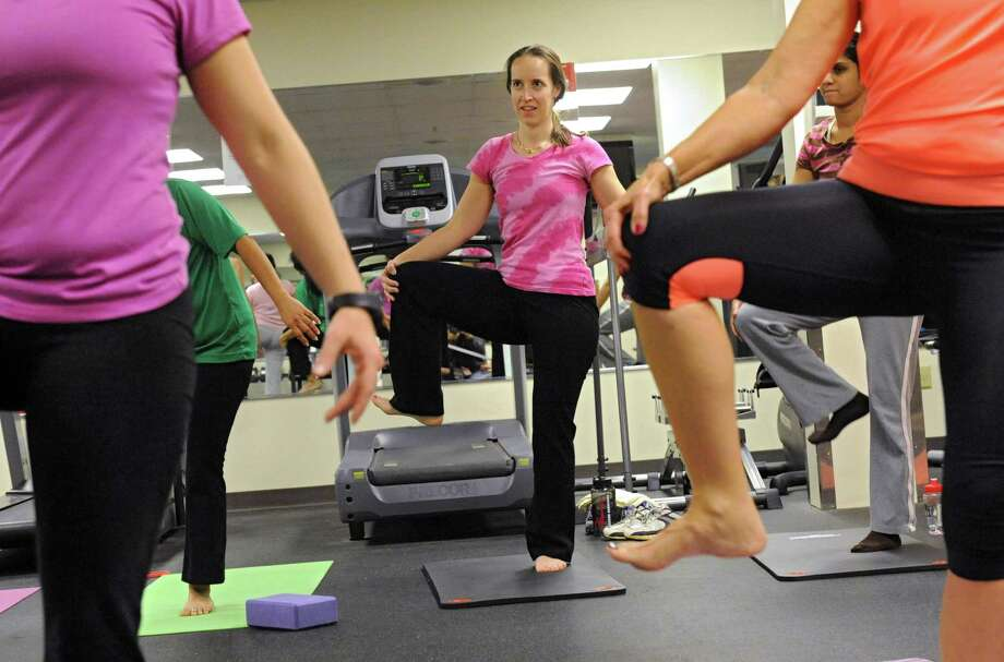 CDPHP employee Tanya LaVallee of Rensselaer, center, takes her first yoga class in a gym at the CDPHP offices at 500 Patroon Creek Blvd. on Wednesday, Jan. 15, 2014 in Albany, N.Y.  More companies are offering fitness classes, Weight Watchers and other health management options to their employees. (Lori Van Buren / Times Union) Photo: Lori Van Buren / 00025367A