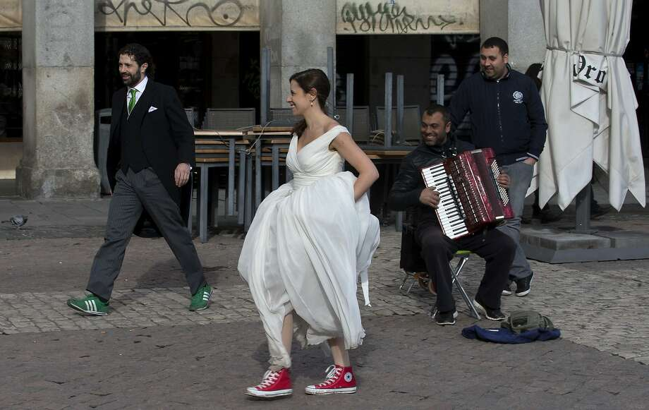 And the bride wore Converse All-Stars high tops: A street musician plays for a couple having wedding photos taken in 