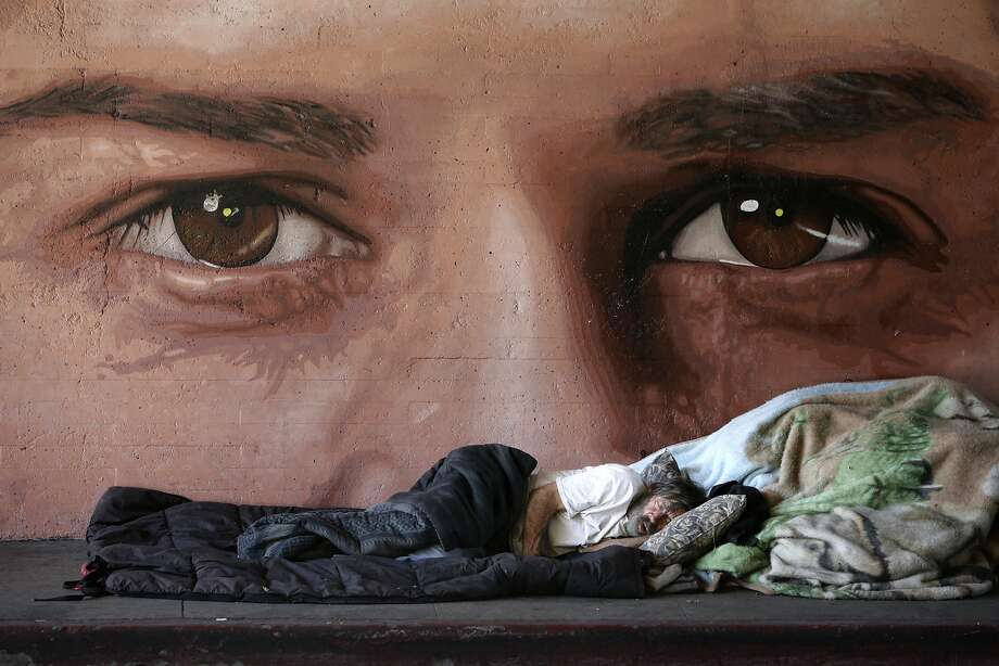 Homelessness at a glance: In Los Angeles, a street person sleeps under unblinking eyes. Photo: Jae C. Hong, Associated Press