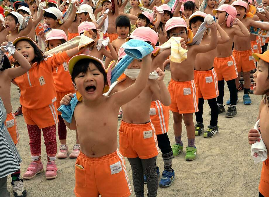 Kindergarteners towel off after working out in a playground at Tokyo's Mizuho school on the day of Daikan, which is   believed to be Japan's coldest day of the year. The kids exercise without shirts every day of the year. Photo: Yoshikazu Tsuno, AFP/Getty Images