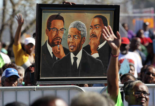 Regina Bell holds up a portrait of Malcolm X, Nelson Mandela and Martin Luther King, Jr, during the 27th anniversary of the Martin Luther King, Jr. Commemorative March and Program at Pittman-Sullivan Park, Monday, Jan. 20, 2014. Photo: JERRY LARA, San Antonio Express-News / © 2014 San Antonio Express-News