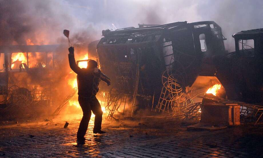 Slinging in Ukraine, just slinging in Ukraine:A protester hurls a stone during clashes with police in the center 