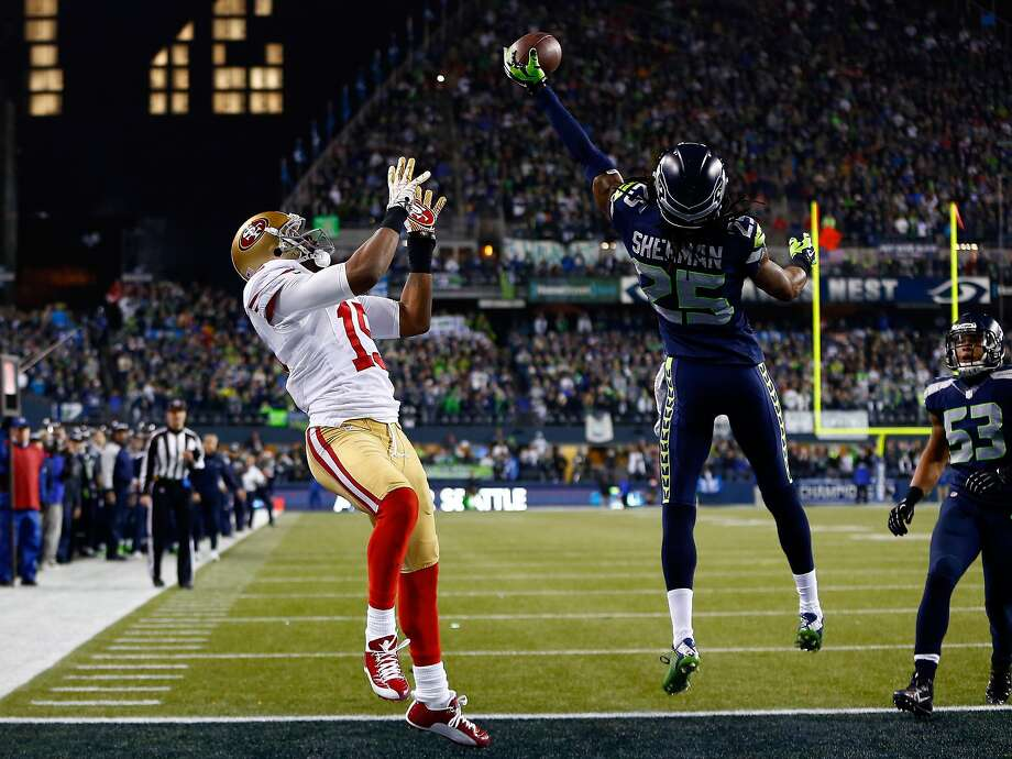 Cornerback Richard Sherman of the Seattle Seahawks tips the ball up in the air as outside linebacker Malcolm Smith catches it to clinch the victory for the Seahawks against the San Francisco 49ers during the 2014 NFC Championship at CenturyLink Field on January 19, 2014 in Seattle, Washington. Photo: Jonathan Ferrey, Getty Images