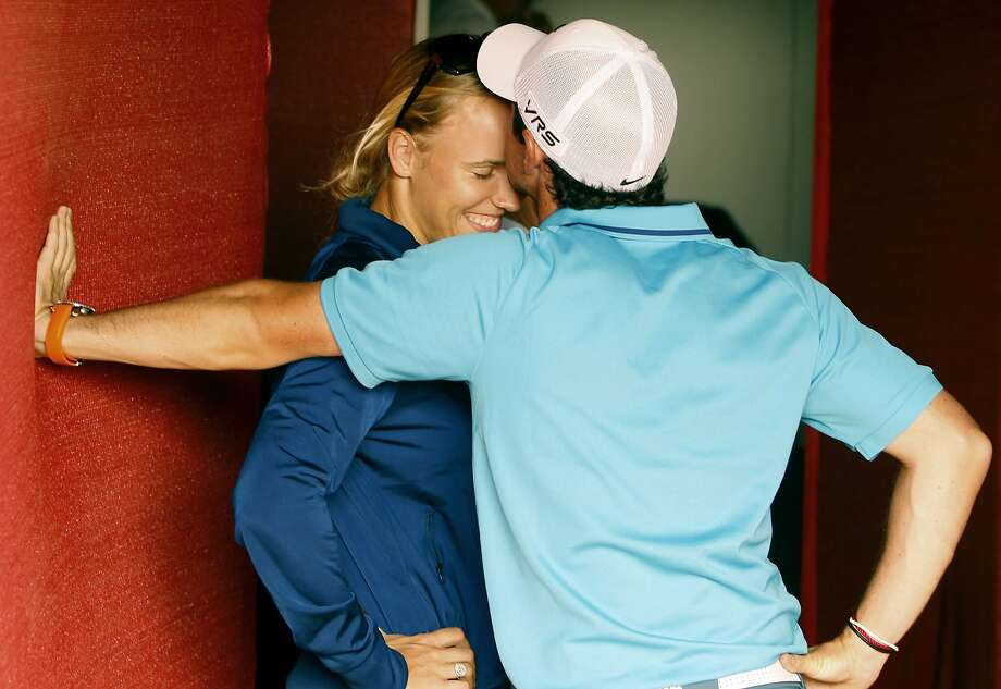 From one loser to another:Rory McIlroy kisses the forehead of his Danish girlfriend, Caroline Wozniacki, after he lost the Abu Dhabi HSBC Golf Championship in the United Arab Emirates by a stroke after taking a two-stroke penalty. Wozniacki flew out to watch McIlroy's final round after she was upset at the Australian Open. Photo: Kamran Jebreili, Associated Press
