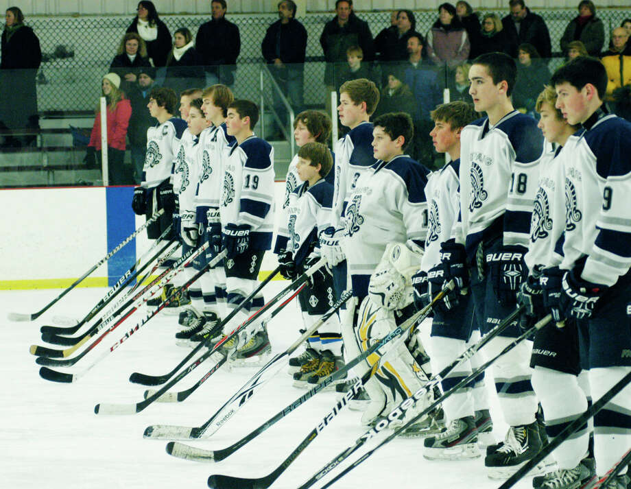 Spartan players stand in unison as the Star Spangled Banner is played before Shepaug Valley High School's co-op ice hockey team played Newtown at The Gunnery in Washington, Jan. 10, 2014 Photo: Norm Cummings / The News-Times