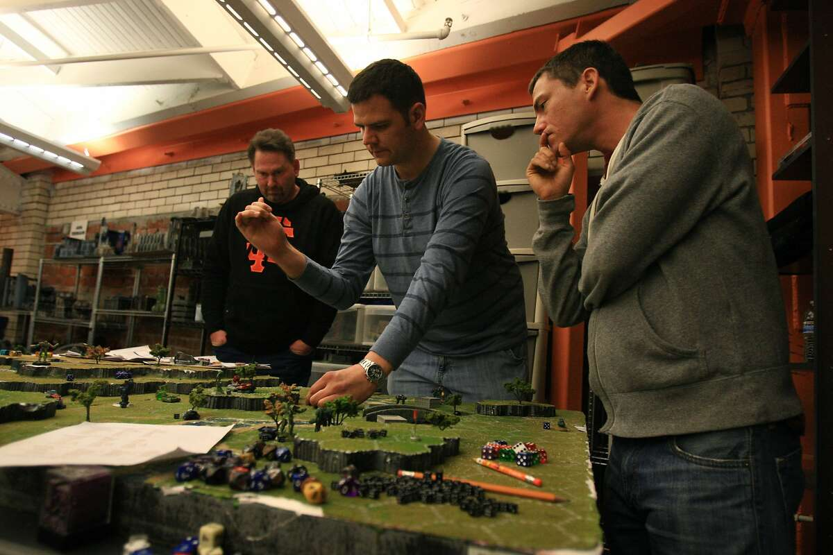 Chris Mortensen, David Ripperda and William Holcomb playing Battletech at the Endgame store in Oakland, Calif. on Saturday, Jan 18, 2014.
