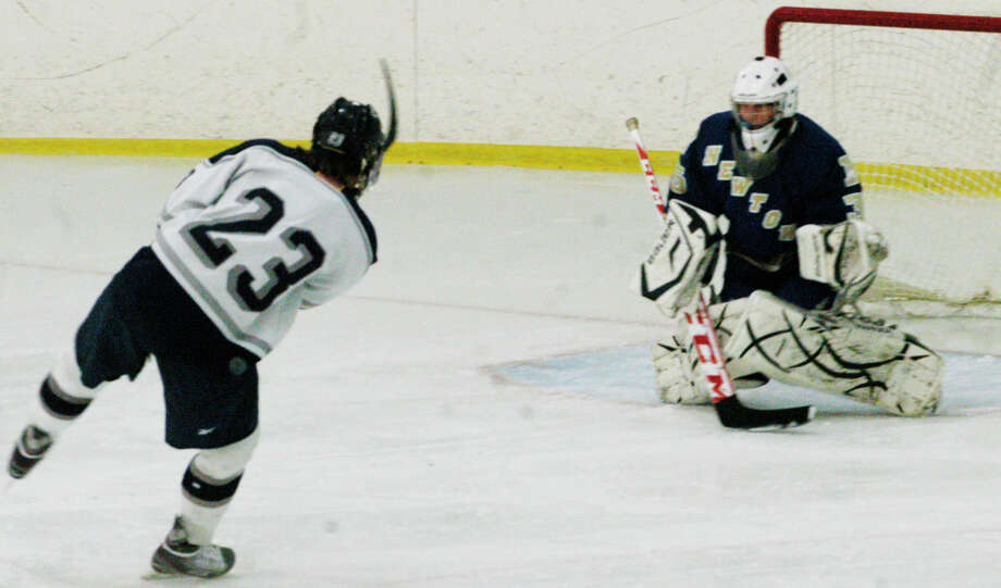 The Spartans' Andrew Loya fires a shot destined for net during Shepaug Valley High School's co-op ice hockey's match vs. Newtown at The Gunnery in Washington, Jan. 10, 2014 Photo: Norm Cummings / The News-Times