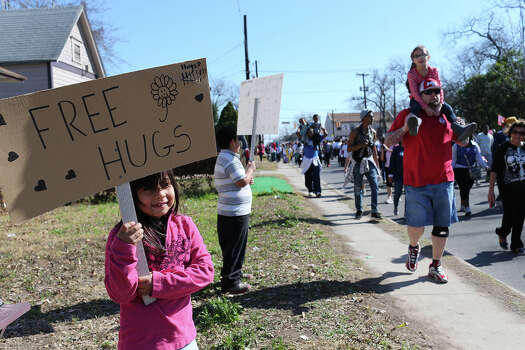 Alondra Ayala, 7, and her brother, Norberto Ayala, 9, offer free hugs to marchers during the 27th anniversary of the Martin Luther King, Jr. Commemorative March and Program, Monday, Jan. 20, 2014. Photo: JERRY LARA, San Antonio Express-News / © 2014 San Antonio Express-News