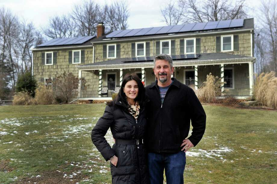 Nina, 44, and David, 50, Stout, stand outside their solar-paneled home in of Newtown, Conn., MOnday, January 20, 2014. Photo: Carol Kaliff / The News-Times