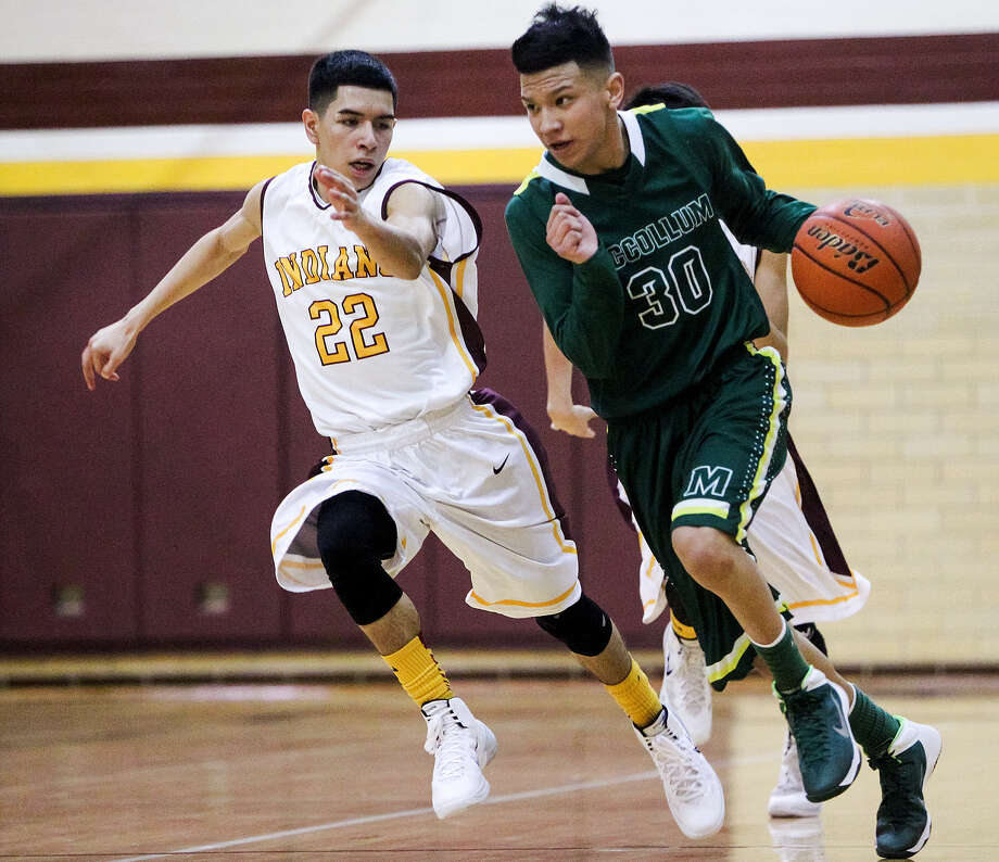McCollum's Angel Loera, right, brings the ball up court as Harlandale's Armando Guerrero applies pressure during their game on Friday. McCollum won 75-68. Photo: Marvin Pfeiffer / Southside Reporter / Prime Time Newspapers 2014
