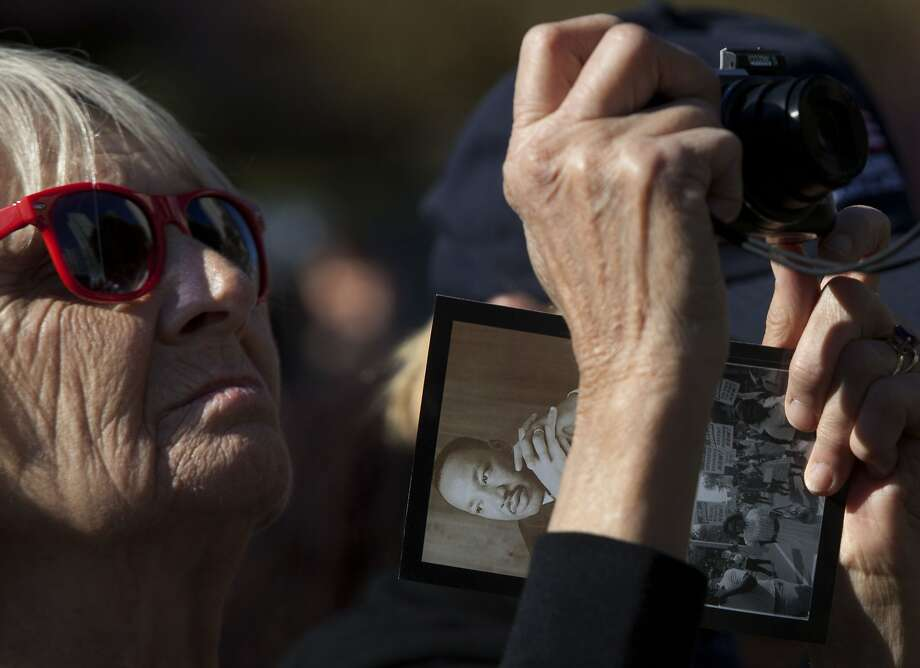 Lesley Grill, a tourist visiting from Australia, takes pictures of the stage at Yerba Buena Gardens in San Francisco during a celebration of Martin Luther King Jr. Day. Photo: Liz Hafalia, The Chronicle
