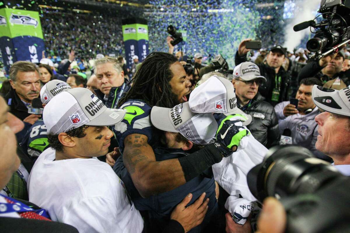 From left, Seattle Seahawks quarterback Russell Wilson, looks on as Richard Sherman embraces coach Pete Carroll (obscured) and general manager John Schneider as they celebrate after the Seahawks defeated the San Francisco 49ers for the NFC Championship at CenturyLink Field on Sunday, January 19, 2014.